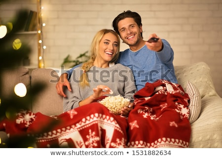 happy couple watching tv at home on christmas stock photo © dolgachov