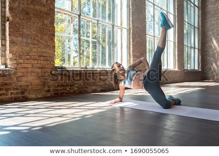 Concept of sport and healthy lifestyle. Strong young beautiful woman is engaged in a gym on an ellip Stock photo © galitskaya