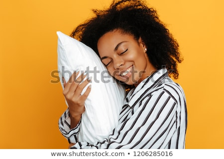 Smiling young african woman hugging pillow Stock photo © deandrobot