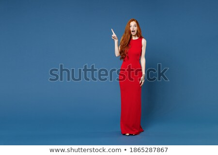 Image of shocked woman wearing red dress pointing finger at herself Stock photo © deandrobot
