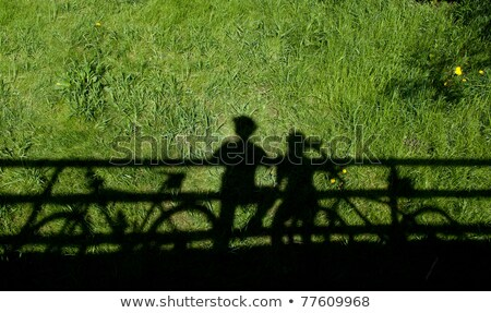 two mountain bikers silhouettes during a halt on a bridge stock photo © lightpoet