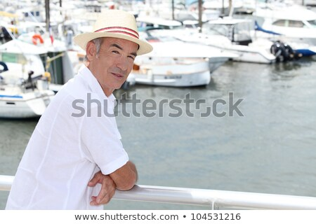 Older man in a straw panama hat standing by a marina Stock photo © photography33