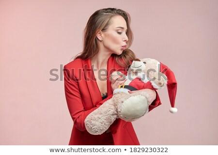 young girl in a santa hat kissing a teddy bear stock photo © stryjek