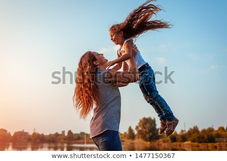 mother lifting child in river stock photo © is2