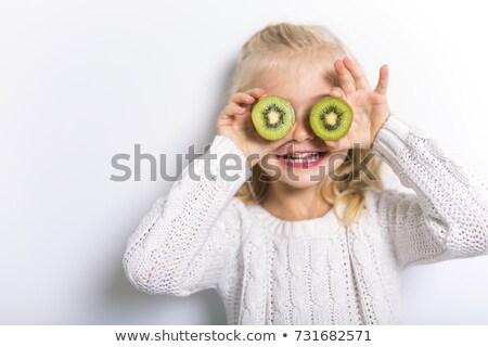 Cute girl 4-5 year old posing in studio with fruit kiwi Stock photo © Lopolo