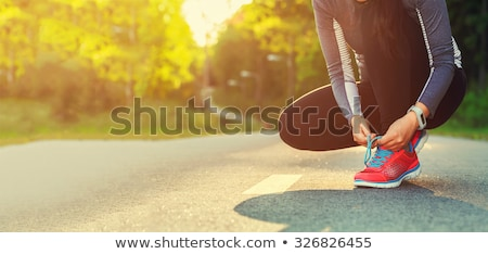 female runner tying her shoes preparing for jogging outside young girld runner getting ready for tr stock photo © galitskaya
