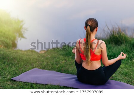 Calm young woman in sports clothing sitting on grass at lake Stock photo © pressmaster