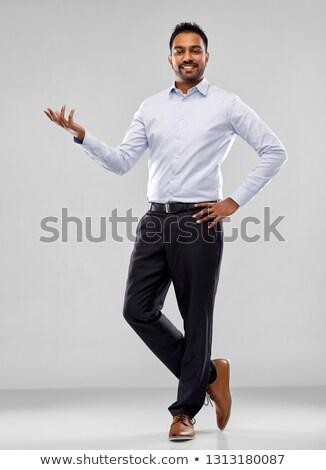 indian businessman holding something over grey stock photo © dolgachov