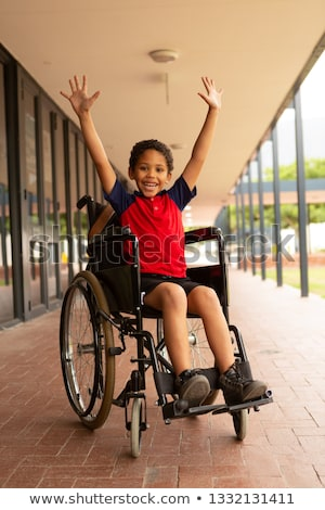Front view of happy mixed-race disabled schoolboy with arms up looking at camera in corridor at elem Stock photo © wavebreak_media