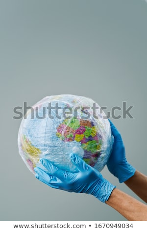 doctor with a world globe wrapped in plastic