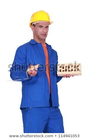 Confused mason holding brick and trowel Stock photo © photography33