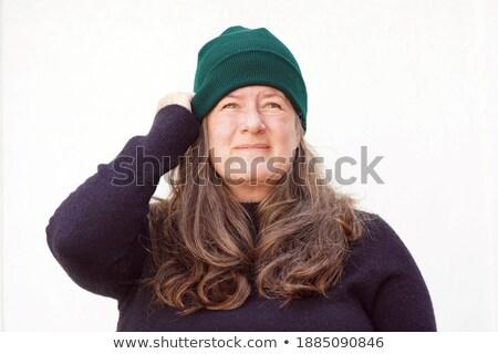 Woman in white holding black hat while smiling Stock photo © wavebreak_media