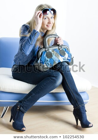 woman wearing blue clothes with handbag sitting on sofa Stock photo © phbcz