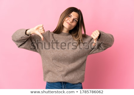 Pretty girl with thumb down gesture Stock photo © Aikon