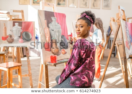 Cheerful woman artist sitting and drawing in art studio Stock photo © deandrobot