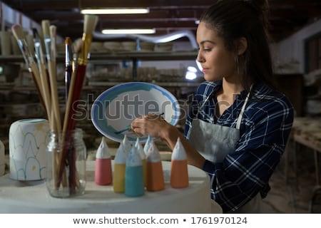 Female potter decorating bowl with paint brush Stock photo © wavebreak_media