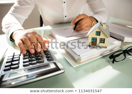 Stock photo: Businessman Calculating Invoice With House Models