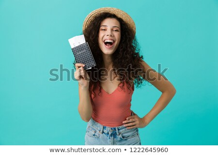Photo of lovely curly woman 20s holding passport and travel tick Stock photo © deandrobot
