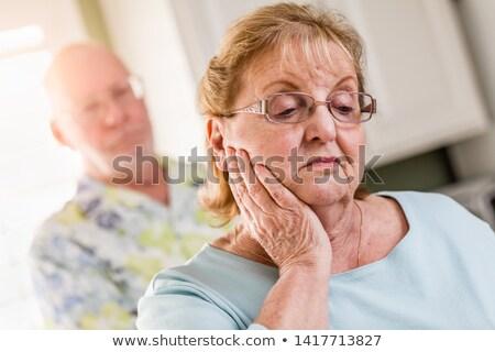 Senior Adult Man Standing Behind Sad Senior Adult Female Stock photo © feverpitch