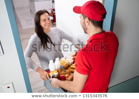 Delivery man giving grocery bag to female customer Stock photo © Kzenon