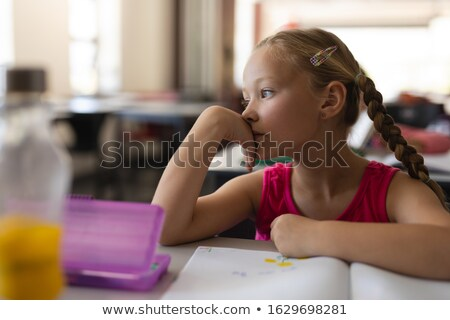 Close-up of thoughtful schoolgirl leaning on desk and looking away in classroom of elementary school Stock photo © wavebreak_media