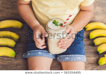 Boy holding a banana smoothie, proper nutrition concept Stock photo © galitskaya