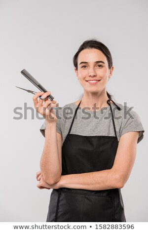 Young cheerful female hairdresser holding hairbrush in front of camera Stock photo © pressmaster