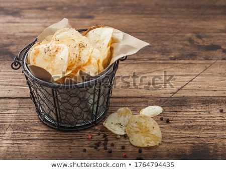 Crunchy potato crisps chips with black pepper in steel snack bucket on wooden background. Stock photo © DenisMArt