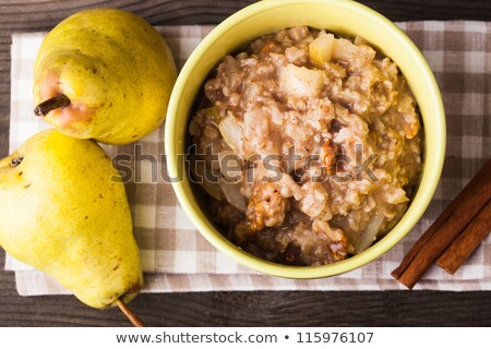 A bowl of porridge with pears slices and walnuts. Stock photo © Illia