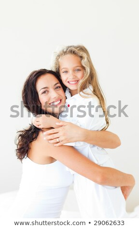 Young Mother and daugther embracing on bed  Stock photo © dacasdo