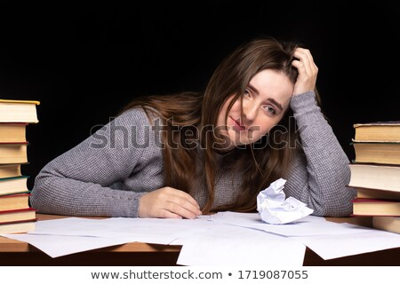 Stock photo: a depressed woman holding in her hands crumpled paper sitting a