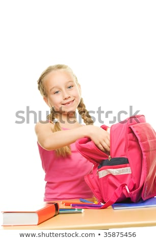 Little schoolgirl packing her rucksack