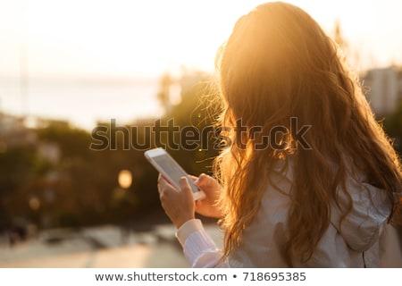Vista laterale bella bruna smartphone bianco telefono Foto d'archivio © wavebreak_media