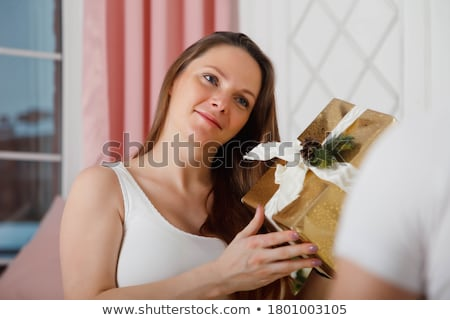 Young pregnant woman accepting present from her husband Stock photo © deandrobot