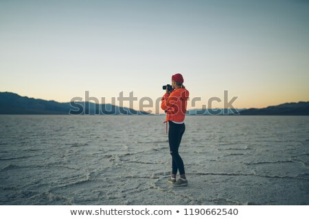 Back view of a young girl taking a picture of a sunset Stock photo © deandrobot