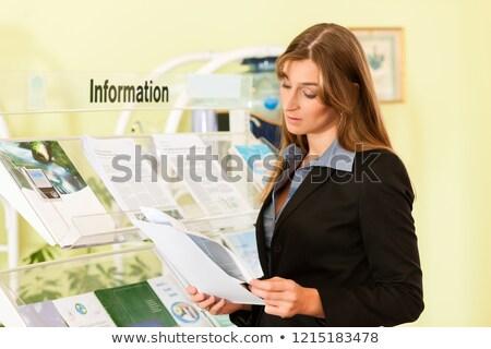 молодые деловая женщина чтение листовка Постоянный стойку Сток-фото © Kzenon