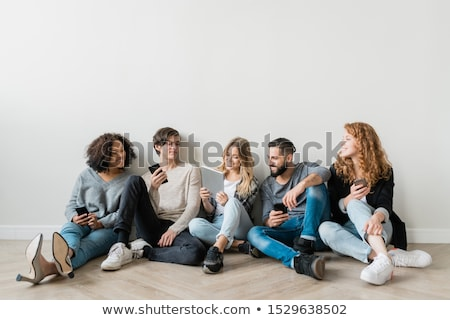 Happy young intercultural friends with gadgets watching funny video Stock photo © pressmaster