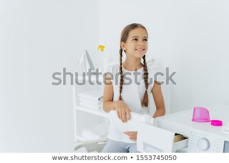 Little happy girl has two pigtails fills in washing machine with liquid detergent, pours into tray o Stock photo © vkstudio