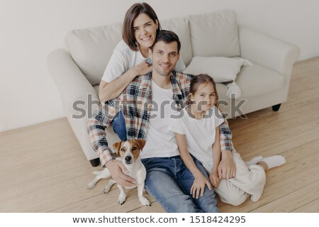 Top view of happy family members pose in spacious room near comfortable sofa, favourite dog poses ne Stock photo © vkstudio