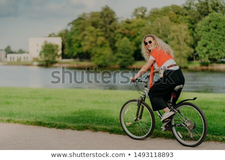 Photo of cheerful woman dressed casually, rides bicycle, looks aside, has happy expression, wears sh Stock photo © vkstudio