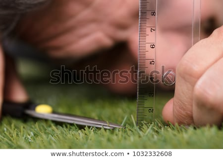 Man Using Measuring Scale While Cutting Grass Stock photo © AndreyPopov