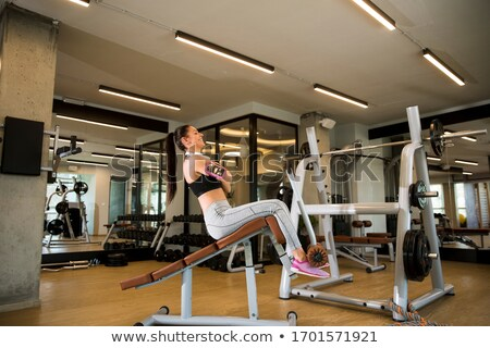 Young woman have a training at sit up bench in the gym Stock photo © boggy