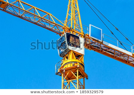 Tall white tower crane against bright blue sky. Stock photo © RuslanOmega