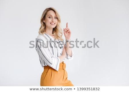 Beautiful female pointing upwards Stock photo © stockyimages