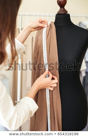 Cropped image of seamstress measuring fabric on black dummy Stock photo © deandrobot