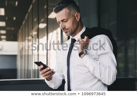 Portrait of a smiling thoughtful man holding mobile phone Stock photo © deandrobot