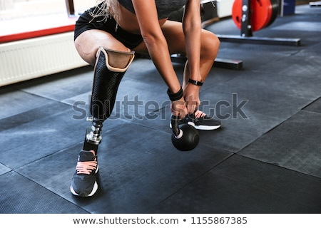 Strong disabled sports woman make sport exercises with equipment in gym. Stock photo © deandrobot