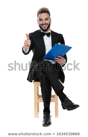 young businessman in black tuxedo sitting on wooden chair Stock photo © feedough