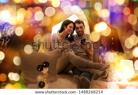 happy couple with smartphone in kids tent at home Stock photo © dolgachov