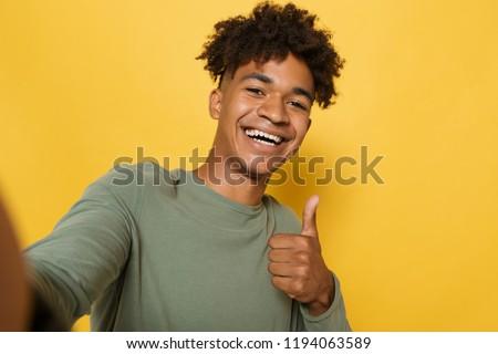 Portrait of satisfied african man having stylish afro hairdo lau Stock photo © deandrobot